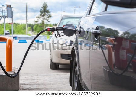 Refilling the car with gasoline at the gas station - stock photo