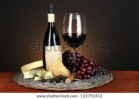 Refined still life of wine, cheese and grapes on wicker tray on wooden table on brown background - stock photo