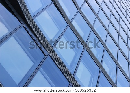 Refined tilt photo of contemporary structural glass facade. Fragment of modern architecture reflecting blue sky. - stock photo