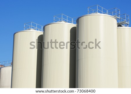 Refinery oil storage tanks and blue clear sky in background