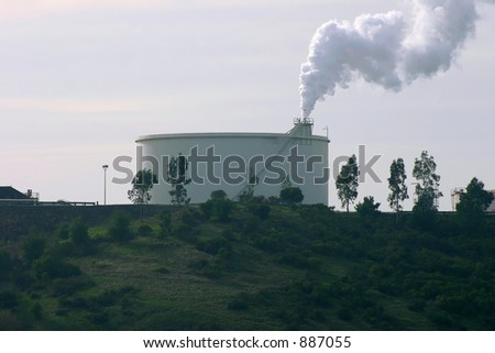 Refinery Tank with Smoke Stack - stock photo