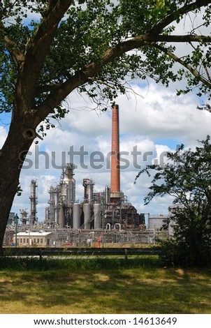 Refinery viewed from roadside with tree and grass. - stock photo