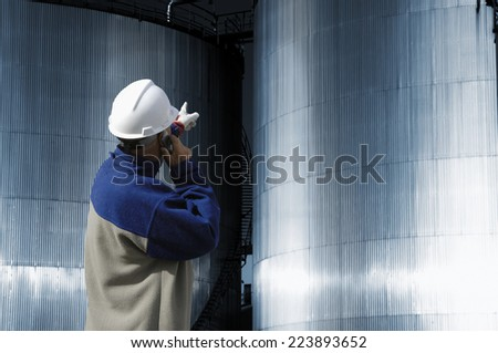 refinery worker in hard-hat pointing at industrial fuel and oil tanks - stock photo
