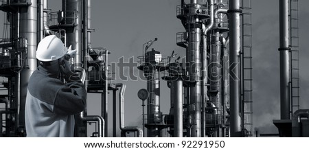 refinery worker, talking in phone, large oil and gas installation in background, duplex blue toning concept - stock photo
