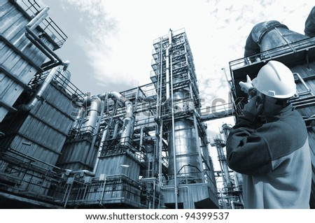 refinery worker with large chemical industry in background, duplex blue toning idea - stock photo