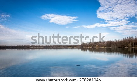 Reflecting blue lake - stock photo