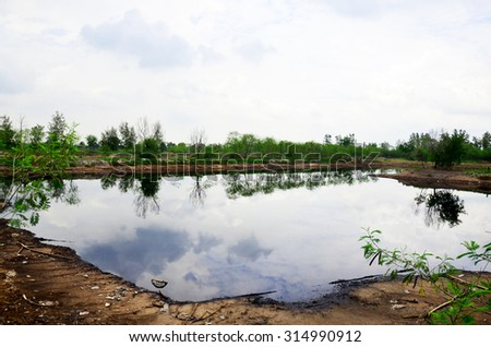 Reflection and Effects Environmental from Water contaminated with Chemicals and oil and This wastewater occur from disposal of Industrial waste and old oil to natural water sources of illicit. - stock photo