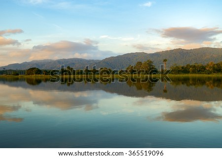 Reflection by the lake with beautiful clouds formation. Nature landscape.