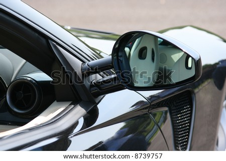 Reflection in a black super car's door mirror - stock photo