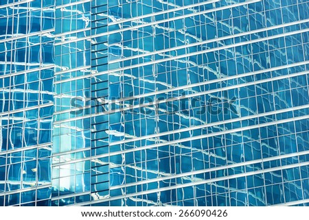 Reflection in blue glass wall of an modern office building. Tint blue