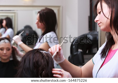 Reflection in mirror. Brunette woman in hairdressing beauty salon. Girl dying hair by hairstylist. hairdresser colouring client hair. - stock photo