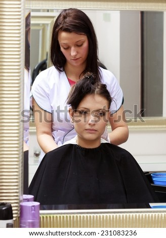 Reflection in mirror. Brunette woman in hairdressing beauty salon. Girl dying hair by hairstylist. hairdresser colouring client hair.
