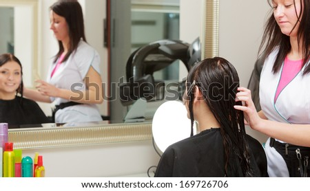 Reflection in mirror. Hairstylist hairdresser by work combing hair of female client. Woman in hairdressing beauty salon.