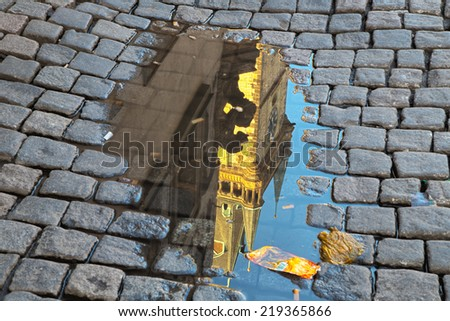 Reflection in rainy puddle of the medieval astronomical clock in the Old Town square in Prague - stock photo