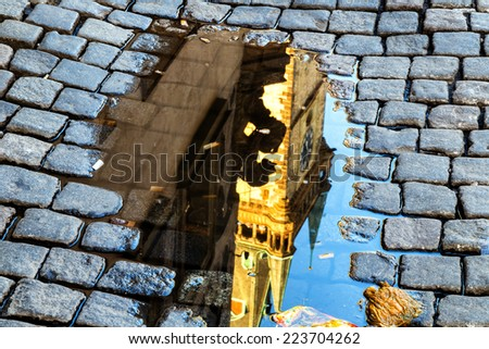 Reflection in rainy puddle of the medieval astronomical clock in the Old Town square in Prague