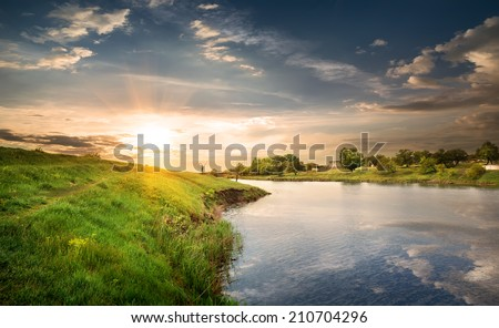 Reflection in the calm river at sunset - stock photo