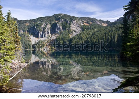 Reflection in the clear mountain lake - stock photo