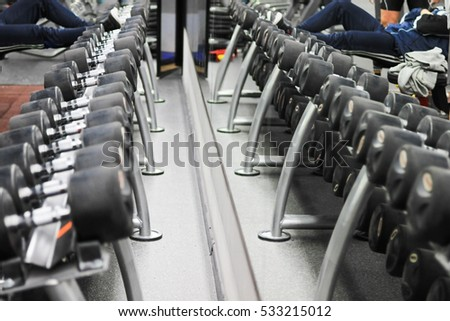 Reflection in the mirror of dumbbells. Background for sports reporting. Close up