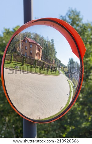 reflection in the mirror of the road from a stone blocks at the house, green grass and forest  - stock photo