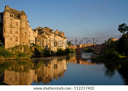Reflection in the river of Espalion old palace in Aubrac, France - stock photo