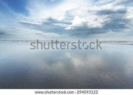 Reflection of a cloud on a wet shoreline - stock photo