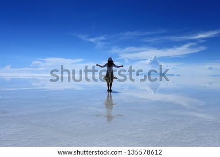 Reflection of a girl in Uyuni Salt Flat, Bolivia - stock photo