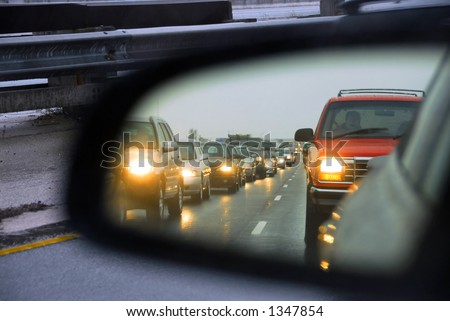 Reflection of a traffic jam in a sideview mirror - stock photo