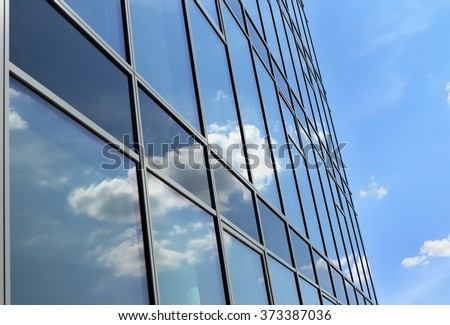 Reflection of cloudy sky in glass wall of modern office building