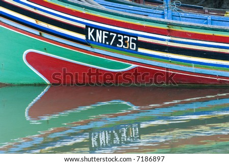 Reflection of colorful traditional boats in Sabak, Kelantan, Malaysia.