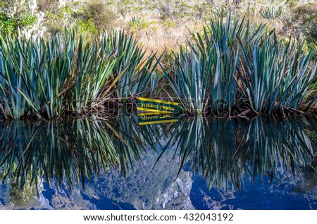 Reflection of Earl Mountains and signage of the Mirror Lakes on the Mirror Lakes which is located at the Milford Road,it is one of the New Zealand's great scenic routes. - stock photo
