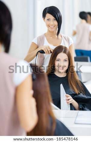 Reflection of hair stylist doing hair style for woman in hairdress salon. Concept of fashion and beauty - stock photo