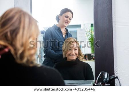 Reflection Of Hairdresser Setting Customer's Hair - stock photo