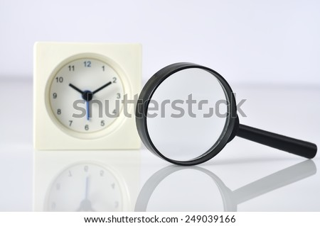 Reflection of Magnifying Glass and Clock, Searching Quality Time Concept and Focus on Magnifying glass - stock photo
