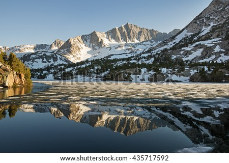 reflection of Mount Goode in the Sierra Nevada mountains reflected in long lake as the ice melts in the spring - stock photo