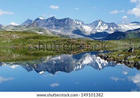 Reflection of mountain chain in a small lake in Jotunheimen national park in Norway. - stock photo