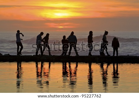 Reflection of people walking on a ledge between the ocean and pond - stock photo
