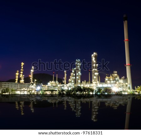 Reflection of petrochemical industry on sunset dark blue sky. - stock photo