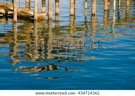 Reflection of piles and a staircase of landing stage in water; Reflections on water surface; Part of a pier - stock photo