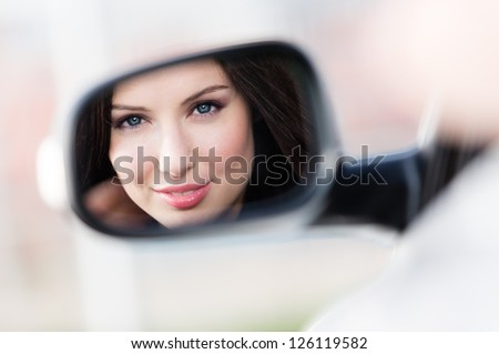 Reflection of pretty woman in the side-view mirror of the car that she took to have a little trip - stock photo