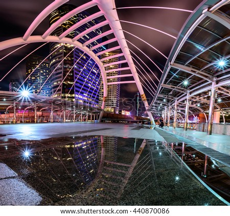 Reflection of Public sky-walk at sky-train station 'Chong Nonsi' at night in Bangkok. - stock photo