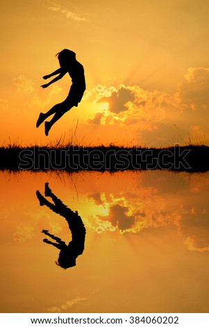 Reflection of  Reflection of Happy woman jumping and sunset silhouette,water reflect - stock photo