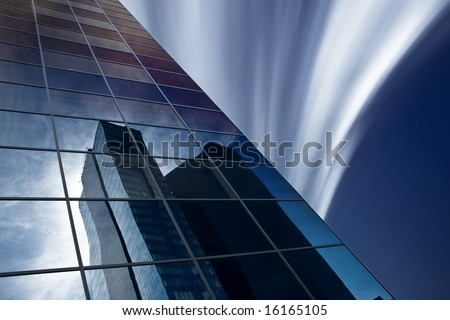 Reflection of skyscraper in windows of other office building. Psychedelic sky. - stock photo