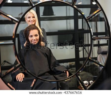 Reflection of smiling hairdresser setting customer's hair - stock photo