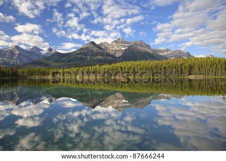 Reflection of snow mountains in smooth water of Herbert Lakes (Banff National Park, Alberta, Canada) - stock photo