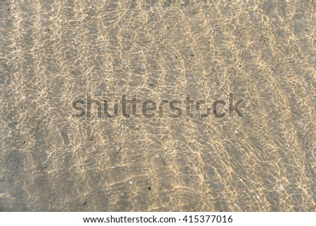 Reflection of sunrise on sea water with sand pattern - stock photo