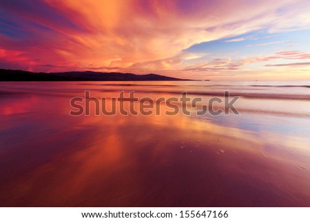Reflection of sunset colors at a beach in Sabah, Malaysia - stock photo