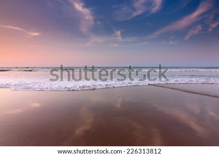 Reflection of sunset sky on a beach in Sabah, East Malaysia, Borneo - stock photo