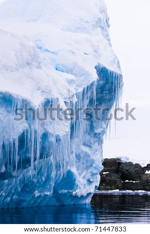 Reflection of the Antarctic Glacier with icicles - stock photo