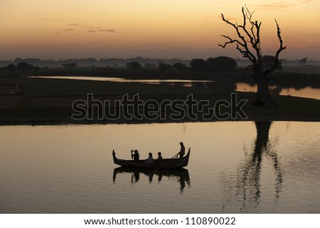 reflection of the boat floating near the dry tree, sunrise