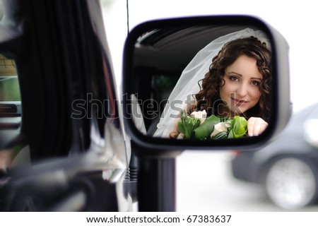 reflection of the bride's face in the rearview mirror in the car